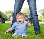 Cute Baby Boy Sitting In Front Of Mother In Park Royalty Free Stock Photography