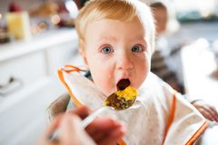 Baby boy sitting in highchair eating Royalty Free Stock Photo