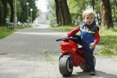 Free Cute Baby Boy Sitting On A Toy Motorcycle In The Park. Copy Space Royalty Free Stock Photography - 138580997