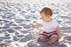 Cute baby boy sitting and playing with sand. On the beach at sunset Royalty Free Stock Photos