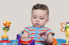 Cute baby boy sitting and playing with toys. Stock Photo