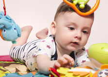 Cute baby boy sitting on a playmat and playing with toys. Royalty Free Stock Images