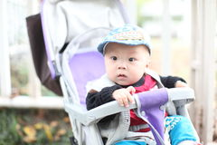 Cute baby boy sitting in stroller Stock Images