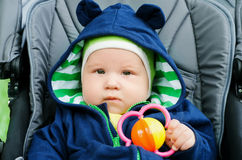 Cute baby boy sitting in the stroller. Cute baby boy with a rattle sitting in the stroller Stock Image