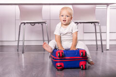 Cute baby boy sitting in the suitcase. Adorable kid going to a cruise royalty free stock photo