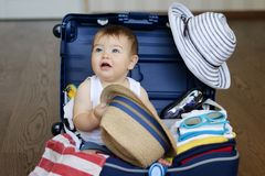 Cute baby boy sitting in the suitcase with hat in his hands, packed for vacation Royalty Free Stock Photo
