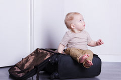 Cute baby boy sitting in the suitcase. An infant kid unpacking his bag.. Adorable kid going to a cruise.  Stock Image