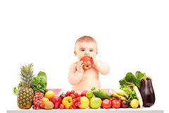 Cute baby boy sitting on a table with fruits and vegetables and Stock Images