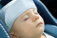 Cute baby boy sleeping in car. Cute baby boy in peaked cap sleeping in a car Stock Photo