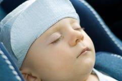 Cute baby boy sleeping in car. Cute baby boy in peaked cap sleeping in a car stock photo