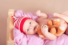 Cute baby boy sleeping with teddy bear in bed Stock Photos