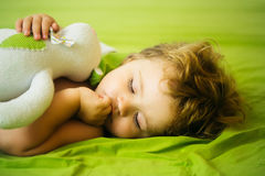 Cute baby boy sleeps. Cute baby boy child with blond curly hair sleeps peacefully with soft toy in bed on green sheet Stock Image