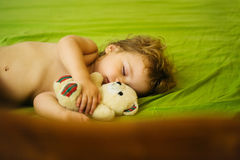 Cute baby boy sleeps. Cute baby boy child with blond curly hair sleeps peacefully with soft toy in bed on green sheet Stock Photography