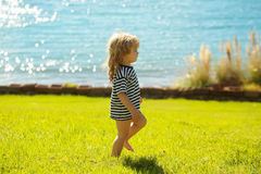 Cute baby boy in striped tshirt walks on green grass Stock Photo