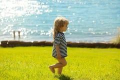 Cute baby boy in striped tshirt walks on green grass Stock Image