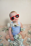 Cute baby boy in sunglasses playing with money, hundreds of dollars