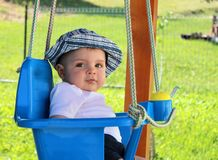 Cute baby boy on a swing outdoor royalty free stock photos