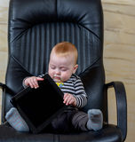 Cute Baby Boy with Tablet Sitting on Office Chair Stock Image