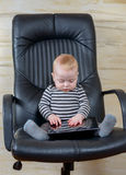 Cute Baby Boy with Tablet Sitting on Office Chair Stock Photos