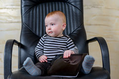 Cute Baby Boy with Tablet Sitting on Office Chair Stock Photography
