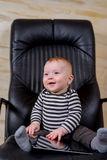 Cute Baby Boy with Tablet Sitting on Office Chair Royalty Free Stock Photos