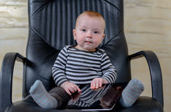 Cute Baby Boy with Tablet Sitting on Office Chair Royalty Free Stock Images