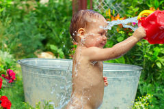 Cute baby boy takes water procedures, summer. Cute baby boy taking water procedures in summer garden Royalty Free Stock Photos