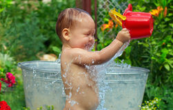 Cute baby boy taking water procedures in garden Stock Photography