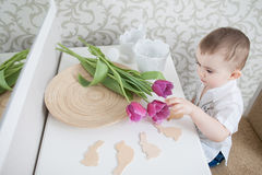 Cute baby boy with tulip Royalty Free Stock Images