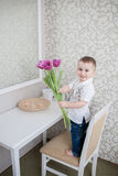 Cute baby boy with tulip Royalty Free Stock Photos