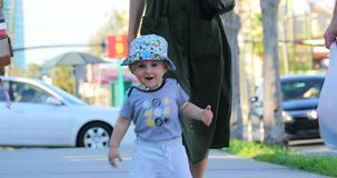 Cute baby boy walking with his mother on the street stock footage