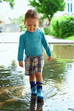 Cute baby boy walking through the puddle. Outdoor Stock Photos