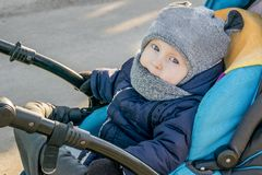 Cute baby boy in warm clothes in pram during winter snow fall on cold winter day. Happy carefree childhood. Little boy sitting in a baby carriage on the street Royalty Free Stock Photos