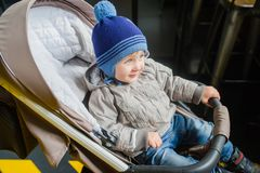 Cute baby boy in warm clothes sits in a stroller indoors royalty free stock image