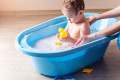 Cute baby washing in blue bath in bathroom. Boy is playing with a yellow duck and soap foam. Cute baby boy washing in blue bath in bathroom. The child is playing stock images
