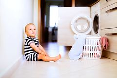 Baby boy by the washing mashine in the kitchen. Royalty Free Stock Photography