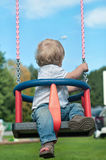 Cute baby boy watching back on swing Royalty Free Stock Image