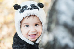 Cute baby boy wearing a Panda bear suit. Happy child in autumn park royalty free stock photo