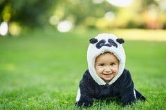 Cute baby boy wearing a Panda bear suit sitting in grass at park. Cute baby boy wearing a Panda bear suit sitting in green grass at park royalty free stock photography
