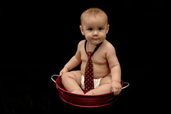 Cute baby boy wearing tie in red pan Stock Images