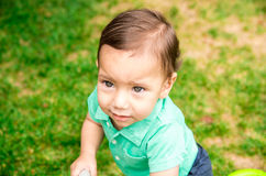 Cute baby boy wearing turquoise t-shirt and combed hair, sitting outside on grassy surface playing around Stock Photos