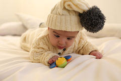 Cute baby boy, wears knitted clothes,playing with toy at cozy home Royalty Free Stock Photos