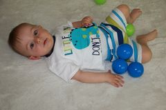 A cute baby boy is playing balls. A cute baby boy on a white background is playing with balls royalty free stock photos