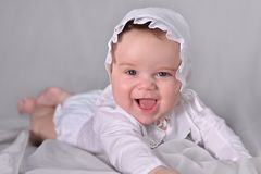 Cute baby boy in white suit crawling stock photo