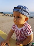 Cute Baby Boy 1 Year Wearing Striped Clothes. Cute Baby Boy 1 Year Wearing A Cap Backwards And Striped Clothes, Close Up Portrait. Mediterranean Sea In The royalty free stock image