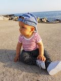Cute Baby Boy 1 Year Wearing Striped Clothes. Cute Baby Boy 1 Year Wearing A Cap Backwards And Striped Clothes, Close Up Portrait. Mediterranean Sea In The royalty free stock images