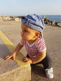 Cute Baby Boy 1 Year Wearing Striped Clothes. Cute Baby Boy 1 Year Wearing A Cap Backwards And Striped Clothes, Close Up Portrait. Mediterranean Sea In The royalty free stock photos