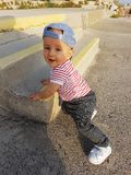 Cute Baby Boy 1 Year Wearing Striped Clothes And Standing On The. Cute Baby Boy 1 Year Wearing A Cap Backwards And Striped Clothes, Close Up Portrait, Baby royalty free stock photo