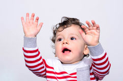 Cute baby boy yelling raising his hands up. Stock Image