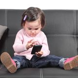 Cute baby browsing in a smartphone. Sitting on a black couch at home Royalty Free Stock Images